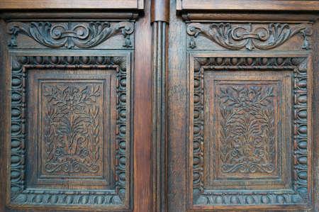 Carved wooden door decoration. Floral motif on door panels. Vintage entrance