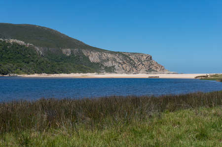 Beautiful landscape with sandy beach, blue water and mountain cliff nature background. Natures Valley, South Africa Stock Photo