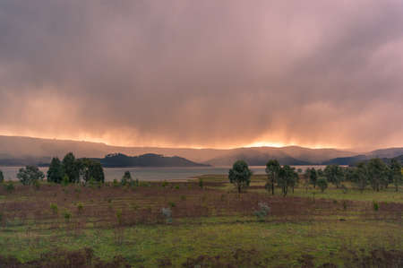 Sunset nature landscape with stormy clouds and rain and beautiful sunlight. Australian nature landscape background, scene