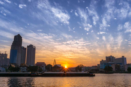 Beautiful sunrise in Bangkok city in Thailand. Asian cityscape with morning sun above the horizon and construction skyscrapers