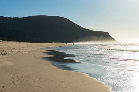Beautiful sunny beach landscape with soft waves and water mist. Summer holiday nature background. Natures Valley, South Africa