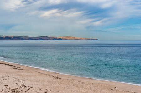 Calm sea and sand beach with distant hills on clear day. Picturesque summer nature background. Carrickalinga beach, South Australia, Australia