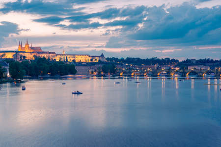 Vltava river with boats, Charles bridge and Prague castle