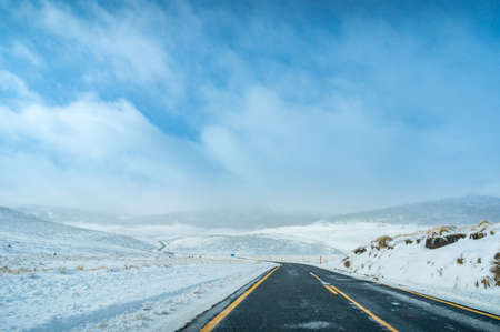 Winter landscape with ice covered asphalt road with yellow dividing lines. Travel in winter