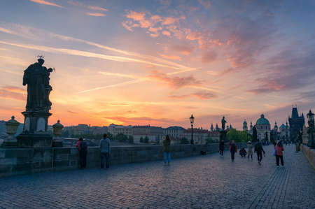 Historic Charles bridge with unidentifiable people taking photos of beautiful sunrise sky. Prague Czech Republic