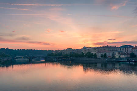 Beautiful sunrise over Vltava river with Prague cityscape and waterfront buildings. Czech Republic Stock Photo