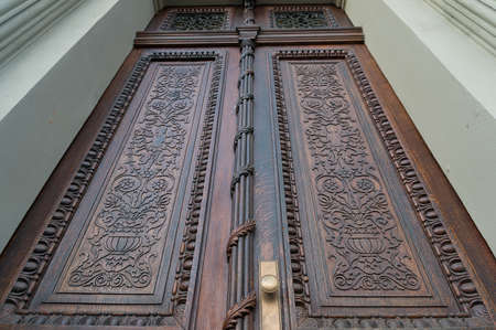 View up on closed wooden carved door. Decorated entrance architecture detail
