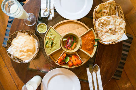 Top view of served Indian cuisine dishes in bowls and white plates. Red and yellow curry and naan with vegetables Stock Photo