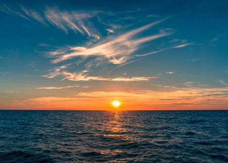 Spectacular sunset with colorful sky and sun going down horizon. Summer beach vacation background
