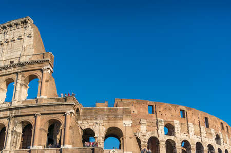 Close up of famous Roman Coliseum landmark with tourists on sunny day. All faces and trademarks are blurred
