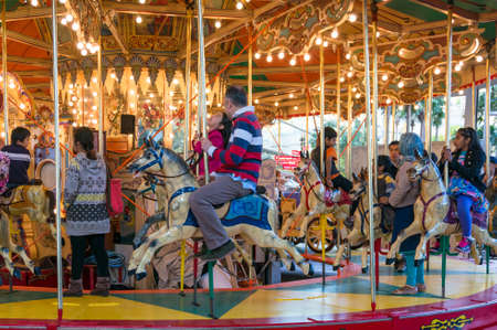 Sydney, Australia - August 04, 2013: Merry-go-round carousel with children and adults having fun in Darling Harbour in Sydney, Australia
