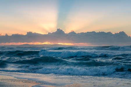 Vista sul mare dell'oceano con onde pesanti e spettacolari raggi del sole o raggi di Dio che brillano attraverso le nuvole. Potenza in natura