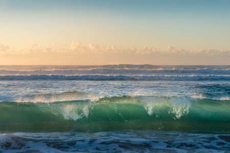 Turquoise blue transparent ocean wave at sunrise. Summer holiday nature background Stock Photo