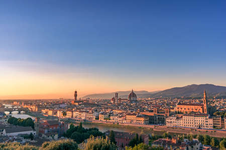 Aerial Florence cityscape with Cathedral of Santa Maria del Fiore and Arno river at sunset with mountains on the background. Travel Italy postcard background