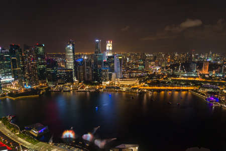 Aerial panorama view of Singapore Central Business District and bay with illuminated office buildings. Singapore cityscape at night background