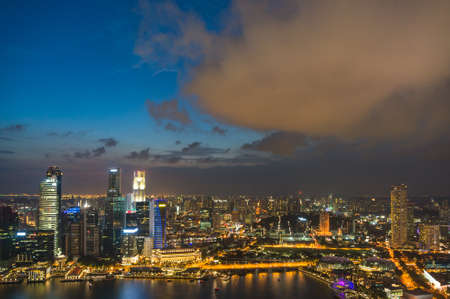 Aerial panorama view of illuminated Singapore Central Business District with office buildings. Singapore cityscape at night background