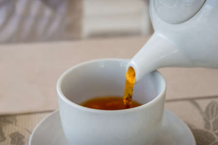 Close up of tea pouring in a white tea cup. Shallow depth of field and elective focus on cups brim