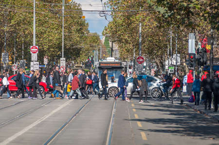 Melbourne, Australia - April 29, 2015: People crossing the road on pedestrian crossing with tramway and cars on the background. City infrastructure