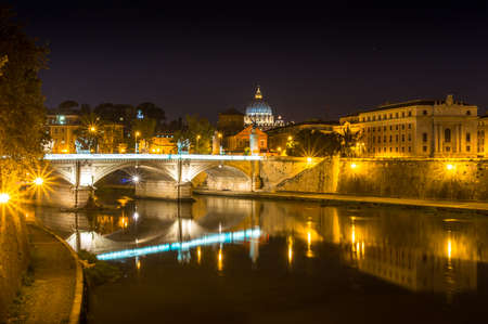 Night Rome cityscape with view of St Peters Basilica in Vatican and bridge across the river. Rome, Italy