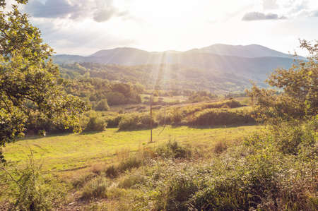 Countryside landscape with green grass and mountains in the distance with sun shining through clouds Stock fotó