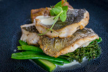 Close up of grilled fish fillets with broccolini florets and green peas and creamy sauce. For styling in upscale restaurant Stockfoto - 130058229