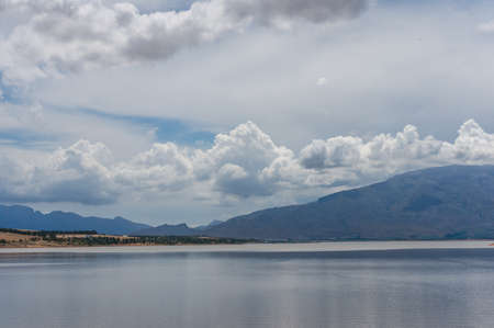 Beautiful nature landscape with lake, mountains and stormy clouds. Western cape, South Africa
