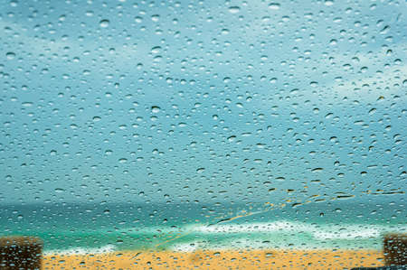 Close up of car windshield with raindrops and sandy beach on the background. Rain season