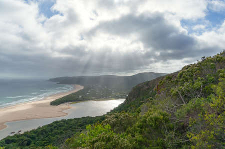 Aerial landscape of beautiful sandy beach with sun shining through clouds and green summer forest on the foreground. Natures Valley, South Africa Stock fotó