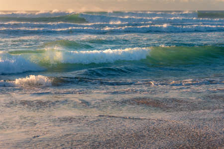 Beautiful stormy waves with water spray moving fast towards seashore. Power in nature background