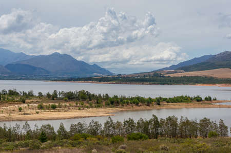 Scenic landscape of lake and mountains on the background. Theewaterskloof Dam in South Africa Banco de Imagens