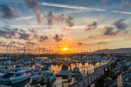 Epic sunset over Coffs Harbour town on Australian coast with yachts and boats in a bay and mountains in the distance,