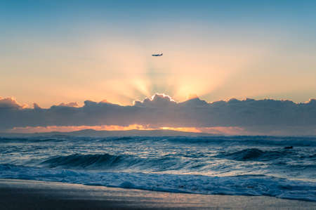 Silhouette of air plane with sun shining through clouds forming god rays and blue ocean beneath