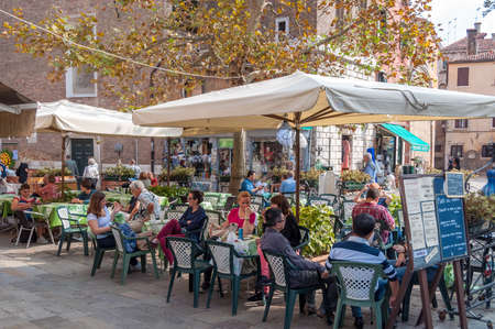 Venice, Italy - September 27, 2013: People dining and relaxing at outdoor restaurant in Venice Editorial