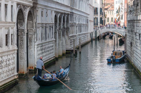 Venice, Italy - September 27, 2013: Venetian canal with tourists in traditional Venetian gondola. Explore Venice and Italy tourism scene