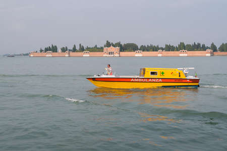 Venice, Italy - September 27, 2013: Bright yellow Ambulance motor boat with captain in front. Venice medical service and medical infrastructure, emergency help