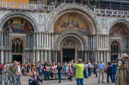 Venice, Italy- September 27, 2013: Tourists on St Mark Square in front of St Mark Cathedral taking photos and enjoying themselves