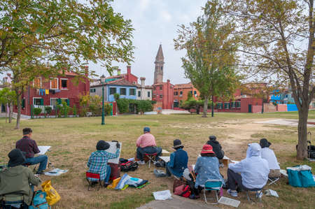 Burano, Italy- September 28, 2013: Group of Asian seniors drawing outdoors historic Italian architecture. Open air drawing class Redakční