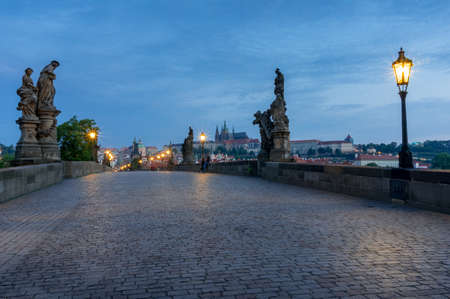 Empty Charles Bridge with street lights at blue hour. Karluv Most at Prague, Czech Republic