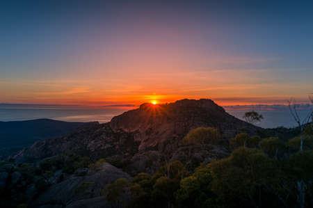 Mountain sunrise landscape. Mountain peak with sun raising above the rock. Beautiful nature scene background. Freycinet National park in Tasmania, Australia Reklamní fotografie