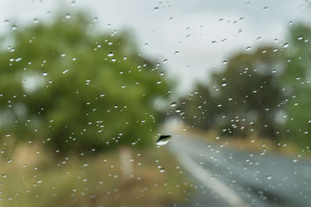 Close up of wet car windshield, windscreen front window with water droplets and blurred road on the background Foto de archivo