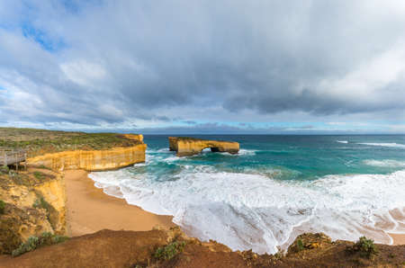 Ocean landscape panorama with spectacular rock formations and sandy beach. London bridge rock formation along Great Ocean Road in Victoria, Australia,