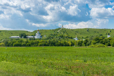 Nature landscape with green grass meadow and churches of Christian monastery with golden cupolas, domes. Holkovsky Monastery, Russia