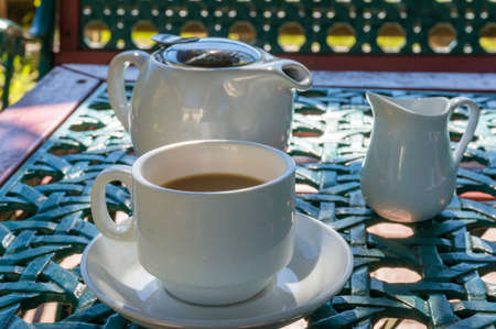 Coffee drink with milk in a white cup on a table outdoors. Coffee, tea break outside. Countryside lifestyle background