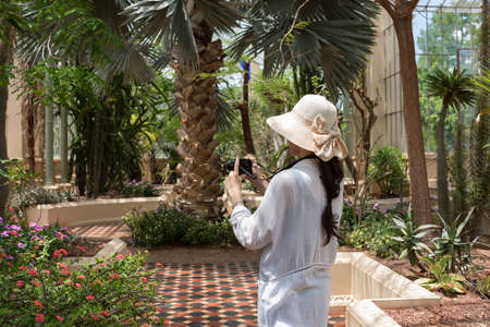 Woman taking photographs of tropical plants with digital camera. Nature photography blogger tourist traveler scene