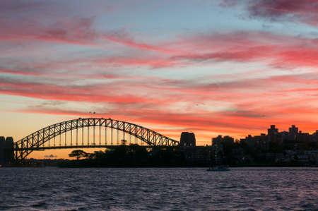Sydney Harbour Bridge landmark against colorful sunset sky. Dark silhouette of Sydney Harbour Bridge popular Australian tourist destination landmark