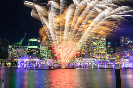 Beautiful vivid fireworks display with cityscape skyscrapers on the background. Sydney Darling Harbour fireworks with modern Business District architecture