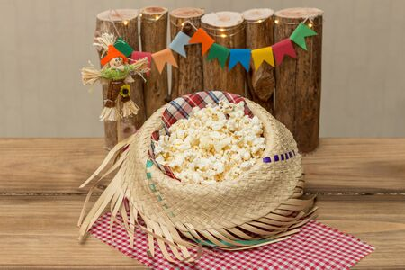 Popcorn served in a straw hat with party june decoration in the background. Festa Junina: Typical Brazilian June party.