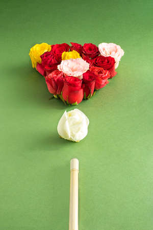 Creative arrangement with colorful flowers on a green background and with a billiard cue. Minimal nature and Mother's day concept.
