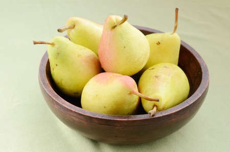 Yellow pears in old wooden bowl on light-green background Stock Photo - 15309784