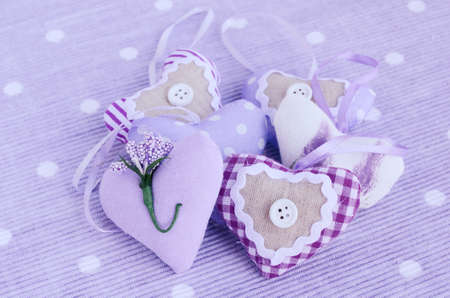 Decorative lavender aroma hearts placed on table napkin of tender lavender color photo